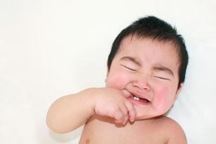 指をくわえて泣く赤ちゃん(白背景)の素材 [FYI00464074]
