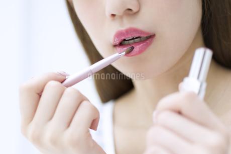 口紅を塗る女性の口元の写真素材 [FYI00465522]