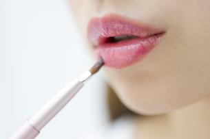 口紅を塗る女性の口元の写真素材 [FYI00465537]