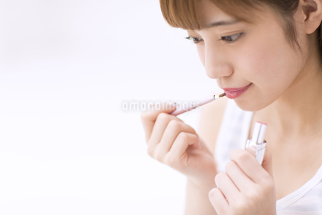 口紅を塗る女性の写真素材 [FYI00465547]