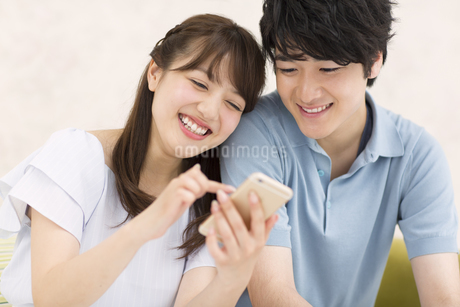 スマートフォンを見るカップルの写真素材 [FYI00465558]