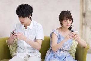 ソファーに座ってスマートフォンを見るカップルの素材 [FYI00465559]