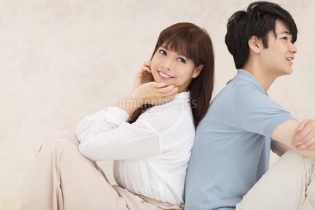 背中を合わせ寄り添うカップルの写真素材 [FYI00465564]