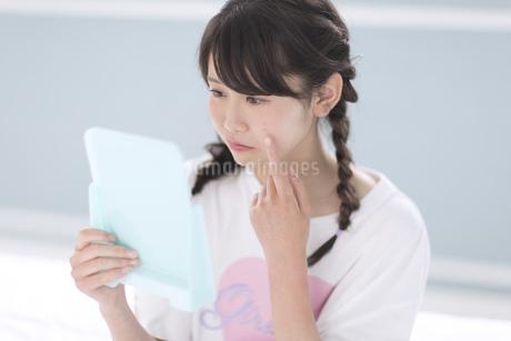 鏡で顔のチェックをする女性の写真素材 [FYI00465569]