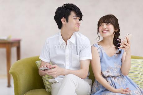 ソファーに座って見つめ合うカップルの写真素材 [FYI00465570]