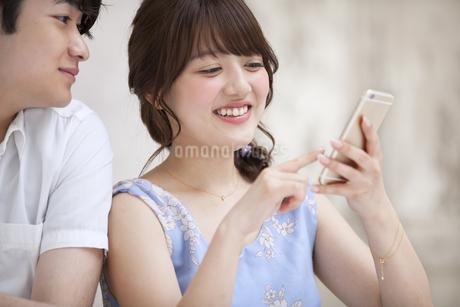スマートフォンを見るカップルの素材 [FYI00465576]
