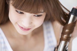 ヘアアイロンで髪を巻く女性の写真素材 [FYI00465587]