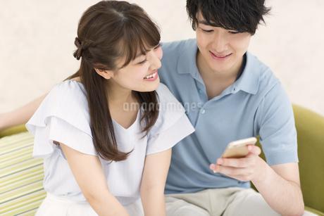 ソファーに座ってスマートフォンを見るカップルの写真素材 [FYI00465589]