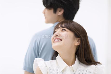 背中を合わせ寄り添うカップルの写真素材 [FYI00465590]