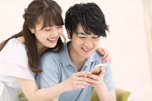 ソファーで寄り添いながらスマートフォンを見るカップルの素材 [FYI00465594]