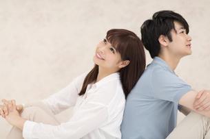 背中を合わせ寄り添うカップルの写真素材 [FYI00465595]