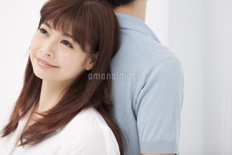 背中を合わせ寄り添うカップルの写真素材 [FYI00465597]