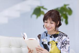ソファーに座って本を読む女性の写真素材 [FYI00465601]