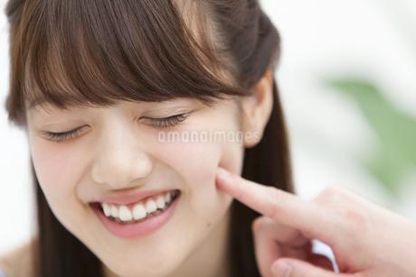 女性の頬を突く男性の手元の写真素材 [FYI00465607]