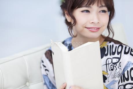 ソファーに座って本を持ち遠くを見つめる女性の写真素材 [FYI00465614]