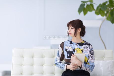 ソファーに座って本を持ち遠くを見つめる女性の写真素材 [FYI00465616]