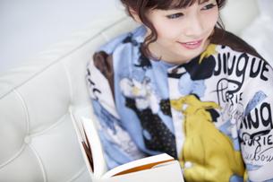 ソファーに座って本を持ち遠くを見つめる女性の素材 [FYI00465618]