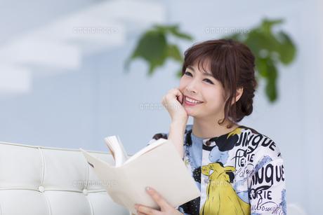 ソファーに座って本を持ち微笑む女性の写真素材 [FYI00465622]