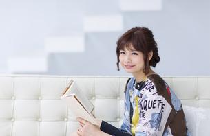 ソファーに座って本を持ち微笑む女性の写真素材 [FYI00465623]