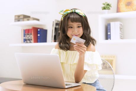 ノートPCの前でカードを手に持ち見つめる女性の素材 [FYI00465629]