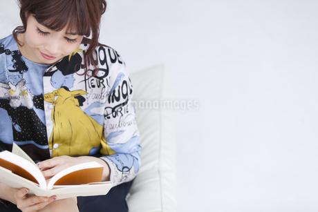 ソファーに座って本を読む女性の写真素材 [FYI00465631]