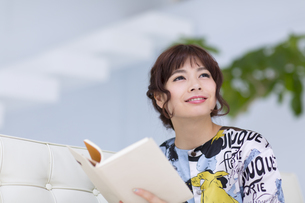 ソファーに座って本を持ち上を見上げる女性の写真素材 [FYI00465633]