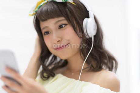 スマートフォンで音楽を聞く女性の写真素材 [FYI00465637]