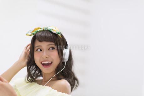 ヘッドフォンをつけ音楽を聞いている女性の素材 [FYI00465639]