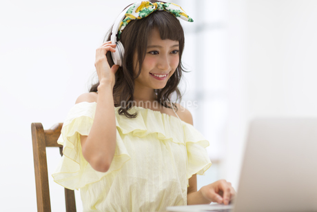 ヘッドフォンをつけながらノートPCを見る女性の写真素材 [FYI00465647]