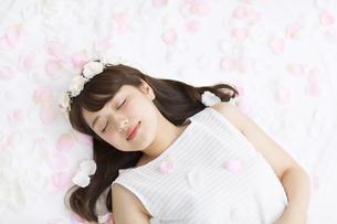 床にまかれた花びらの上に寝転ぶ女性の写真素材 [FYI00465656]