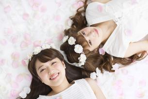 床にまかれた花びらの上に寝転ぶ女性2人の写真素材 [FYI00465670]