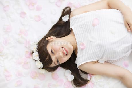床にまかれた花びらの上に寝転ぶ女性の写真素材 [FYI00465671]