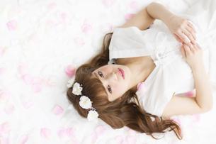 床にまかれた花びらの上に寝転ぶ女性の写真素材 [FYI00465673]