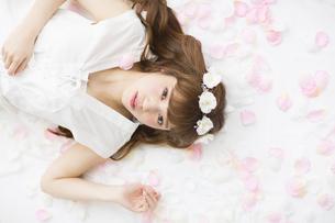 床にまかれた花びらの上に寝転ぶ女性の素材 [FYI00465674]