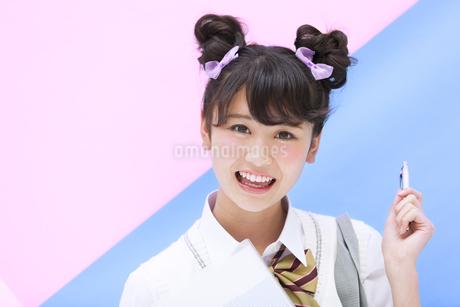 ペンを持って微笑む女子学生の写真素材 [FYI00465677]