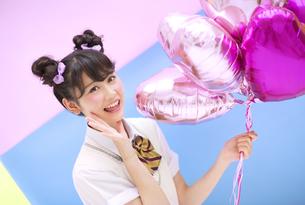 風船を持って笑う女子学生の写真素材 [FYI00465686]