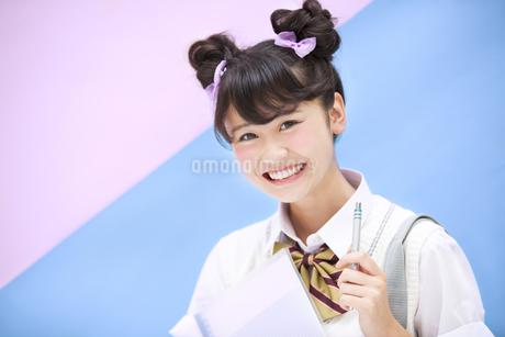 ペンを持って笑う女子学生の写真素材 [FYI00465688]