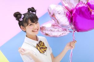 風船を持って笑う女子学生の写真素材 [FYI00465701]