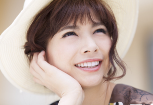 帽子を被って上を見上げる女性の写真素材 [FYI00465720]