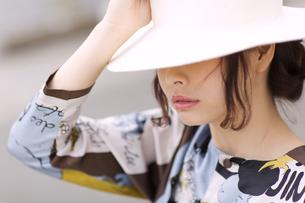 帽子を深く被ってうつむく女性の写真素材 [FYI00465721]