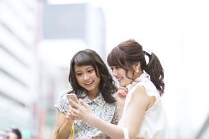 街中でスマートフォンを見る女性2人の写真素材 [FYI00465728]