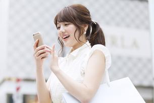 街中でスマートフォンを操作する女性の写真素材 [FYI00465729]