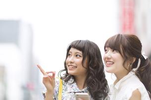 街中でスマートフォンを持ち微笑む女性2人の写真素材 [FYI00465730]