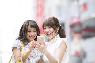 街中でスマートフォンを見る女性2人の写真素材 [FYI00465733]