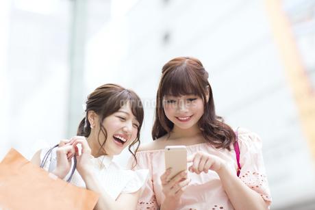 街中でスマートフォンを持ち笑う女性2人の写真素材 [FYI00465734]