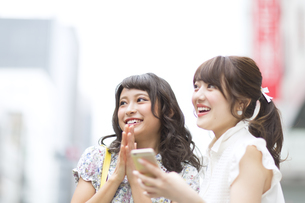 街中でスマートフォンを持ち笑う女性2人の写真素材 [FYI00465735]