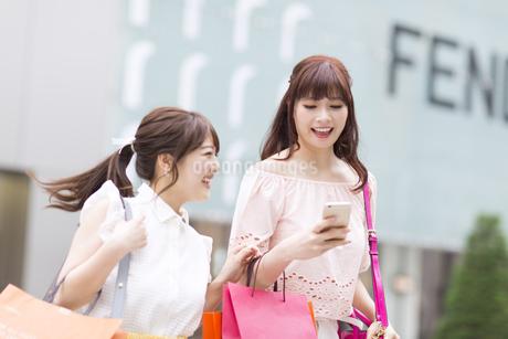 街中でスマートフォンを持ち笑う女性2人の写真素材 [FYI00465737]