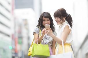 街中でスマートフォンを見る女性2人の写真素材 [FYI00465741]