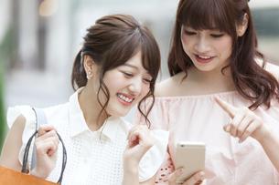 街中でスマートフォンを持ち笑う女性2人の写真素材 [FYI00465743]