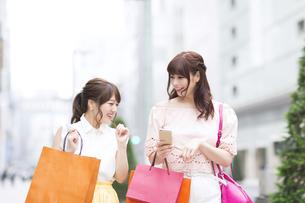 街中でスマートフォンを持ち笑う女性2人の写真素材 [FYI00465744]